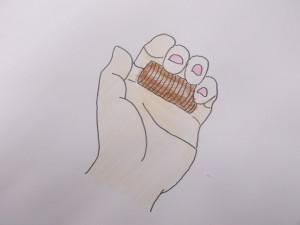 指の付け根で硬貨をまとめる。