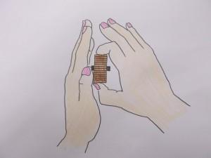 親指と人さし指で硬貨の端をはさみ、硬貨入れ口の上にセットし、ちょっと力を緩める。